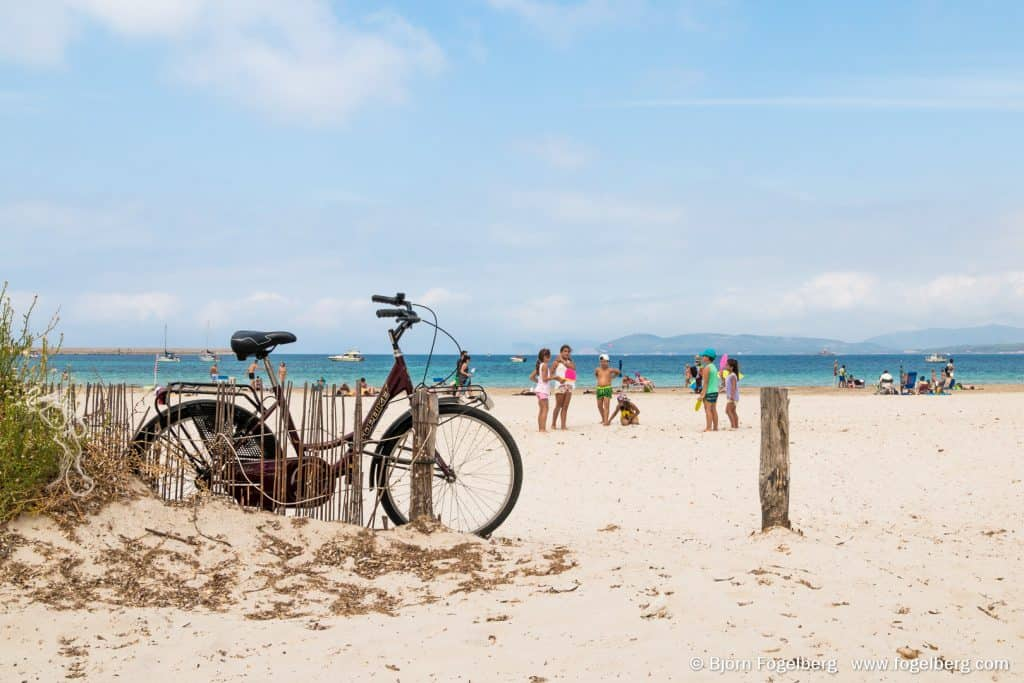 Bicycle and people on the Alghero beach